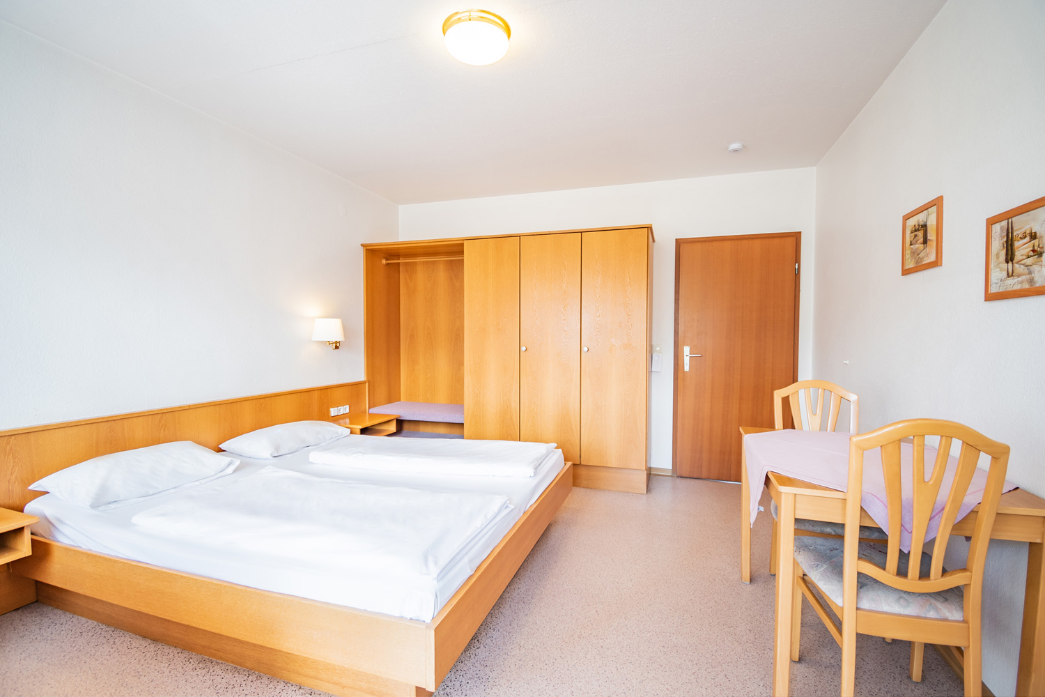 Hotel bedroom with double bed, wardrobe, and table.